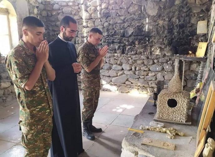 Un sacerdote prega con i soldati