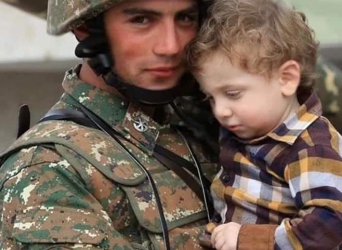 Giovane soldato protegge un bimbo